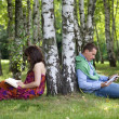 Young couple reading books in park by tree trunk — Stock Photo #3843977