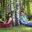 Young couple holding books in park by tree trunk — Stock Photo #3843988