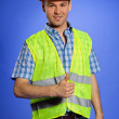 Portrait of architect in coveralls and hardhat showing thumbs up sign - Photo