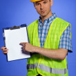 Portrait of architect in coveralls and hardhat pointing at clipboard — Stock Photo #3844251
