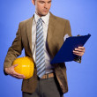 Businessman holding hardhat and looking at clipboard — Stock Photo #3844374