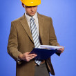 Businessman in yellow hardhat using clipboard — Stock Photo #3844445