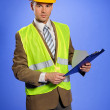 Portrait of businessman in in coveralls using clipboard — Stock Photo