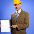 Portrait of businessman in hardhat pointing at clipboard — Stock Photo