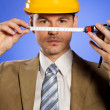 Stock Photo: Portrait of businessman in hardhat holding tape measure