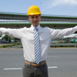 Portrait of architect in hardhat with arm raised at construction site — Stock Photo #3844592