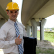 Portrait of architect in hardhat holding laptop bag and showing thumbs up s - Stock Photo
