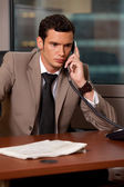 Young businessman talking on telephone in office — Stock Photo