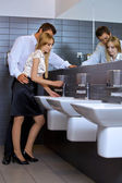 Young business couple flirting with each other at office washroom — Stock Photo