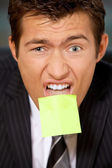 Portrait of businessman in office with blank adhesive note stuck to his chi — Stock Photo