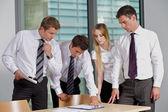 Zespół firmy patrząc na dokument w biurze — Zdjęcie stockowe