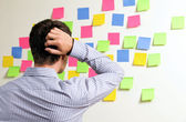 Businessman looking at wall of sticky notes with hands behind head — Stock Photo