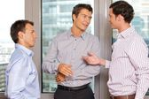 Three businessmen discussing at office — Foto Stock