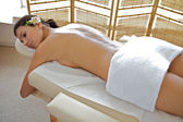 Young woman relaxing on massage table — Stock Photo