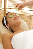 Young woman lying on massage table with cucumber slice being placed over ey — Stock Photo