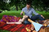 Young man feeding girlfriend at park — Stock Photo