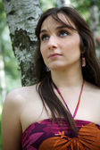 Close-up of young woman standing by tree trunk, looking up — Stock Photo