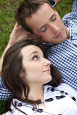 Close-up of young couple relaxing on grass — Stock Photo