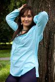 Portret van een jonge vrouw permanent door boom en glimlachen — Stockfoto