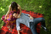 Elevated view of young couple relaxing on sheet in park — Stock Photo