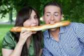 Portrait of young couple eating bread in park — Stock Photo