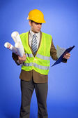 Businessman in coveralls holding blueprint and looking at clipboard — Stock Photo