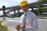 Portrait of architect in hardhat holding blueprint and showing thumbs up si — Stock Photo