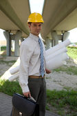 Portrait of architect in hardhat holding blueprint and laptop bag at constr — Stock Photo