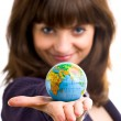 Beautiful woman holds the globe in hand. - Stock Photo