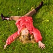 Happy little girl laying on the grass — Stock Photo