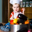 Little boy chef in the kitchen pot — Stock Photo