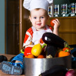 Stock Photo: Little boy chef in the kitchen pot