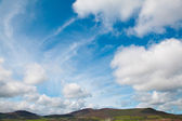 Bright blue sky white clouds over green Irish hills — Stock Photo