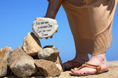 Man holding rock bible verse John 8:7 — Foto de Stock
