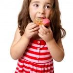 Young girl eating doughnut — Stock Photo