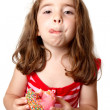 Girl eating doughnut licking lips — Stockfoto
