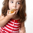 Pretty little girl eating a doughnut — Stockfoto
