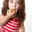 Stock Photo: Pretty little girl eating a doughnut