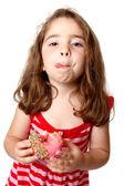 Girl eating doughnut licking lips — Stock Photo