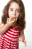 Pretty little girl eating a doughnut — Stock Photo