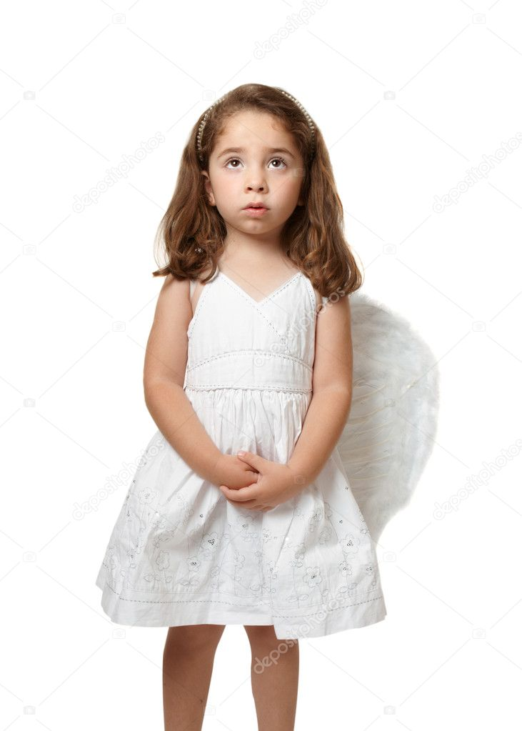 Little angel girl wearing a beautiful white embroidered dress.  She has her hands gently clasped and is looking up toward heaven or sky  Stock Photo #2807899