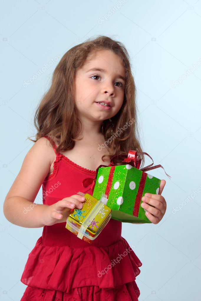 Young preschool girl holding presents.  She is wearing a red dress. — Foto Stock #2808334