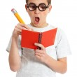 A comical boy student in geeky glasses writing i — Stock Photo #2857358