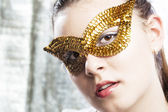 Cute young woman wearing golden mask — Stock Photo