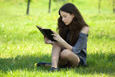 Young student reading book on meadow — Стоковое фото