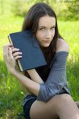 Młody student z książki na łące — Zdjęcie stockowe