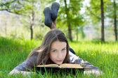Ung student läsa bok i parken — Stockfoto
