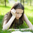 Young student reading book in park — Stock Photo