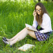 Young schoolgirl in park read book — Stock Photo