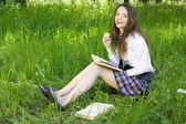 Ung skolflicka i park läsa bok — Stockfoto